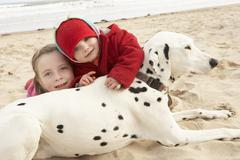 Two girls on beach with pet dog Stock Photos