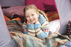 Young girl relaxing inside tent on camping holiday Stock Photos