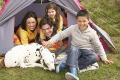 Young family with dog relaxing inside tent on camping holiday Stock Photos
