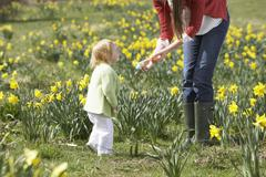 mother and daughter in daffodil field with decorated easter eggs - stock photo