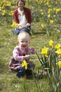 Mother and daughter in daffodil field with decorated easter eggs Stock Photos
