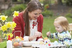 mother and daughter painting easter eggs in gardens - stock photo