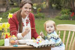 Mother and daughter painting easter eggs in gardens Stock Photos
