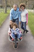 Family having ride in wheelbarrow in countryside Stock Photos