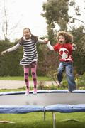 Children playing on trampoline Stock Photos