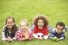 Group of children laying on grass with easter eggs Stock Photos