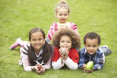 group of children laying on grass with easter eggs - stock photo