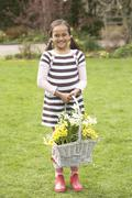 Girl holding basket of daffodils in garden Stock Photos