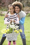 mother and daughter holding basket of daffodils in garden - stock photo