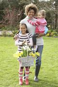 mother and children holding basket of daffodils in garden - stock photo