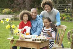 Stock Photo of family painting easter eggs in gardens