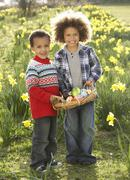 two boys having easter egg hunt in daffodil field - stock photo