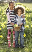 Brother and sister having easter egg hunt in daffodil field Stock Photos