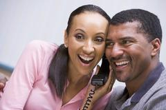 Couple receiving a good news phone call from clinic - stock photo