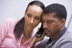 Couple receiving a bad news phone call from clinic - stock photo