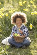 boy on easter egg hunt in daffodil field - stock photo