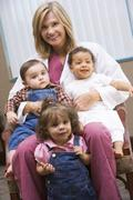 Doctor sitting with three IVF children smiling - stock photo