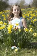 Girl on easter egg hunt in daffodil field Stock Photos