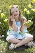 Girl eating chocolate egg on easter egg hunt in daffodil field Stock Photos