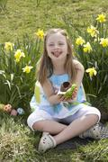 girl eating chocolate egg on easter egg hunt in daffodil field - stock photo