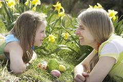 mother and daughter on easter egg hunt in daffodil field - stock photo