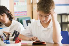 Students in class reading books - stock photo