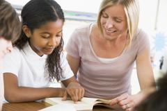 Student in class reading book with teacher - stock photo