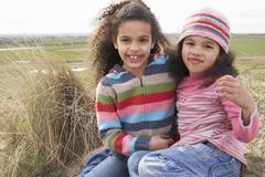 Young girls sitting amongst dunes on winter beach Stock Photos