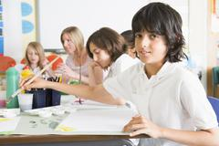 Students in art class with teacher (depth of field) - stock photo