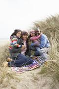 family sitting on blanket in dunes on winter beach - stock photo