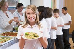 Students in cafeteria line with one holding up her healthy meal and looking at - stock photo