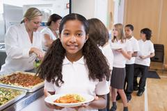 Students in cafeteria line with one holding up her healthy meal looking at - stock photo