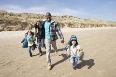 family running on winter beach - stock photo