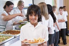 Students in cafeteria line with one holding his unhealthy meal and looking at - stock photo