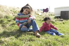 young girls sitting outside in caravan park - stock photo