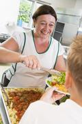 Lunch lady serving salad to student Stock Photos