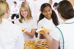 Students in cafeteria line being served by lunch ladies Stock Photos