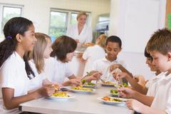 Students sitting at cafeteria table eating lunch (depth of field) - stock photo