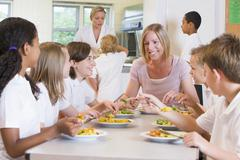 Students sitting at cafeteria table eating lunch with teacher - stock photo