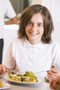 Student in cafeteria eating lunch (selective focus) - stock photo