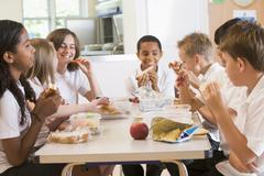 Students sitting at cafeteria table eating lunch (depth of field) Stock Photos