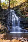 Autumn waterfall in mountain with foliage Stock Photos