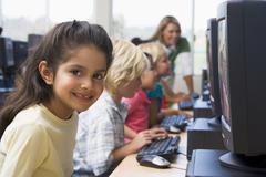 Children at computer terminals with teacher in background (depth of field/high Stock Photos