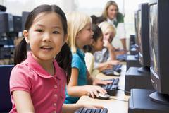 Children at computer terminals with teacher in background (depth of field/high - stock photo