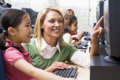 Teacher helping student at computer terminal with students in background (depth Stock Photos