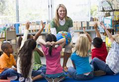 Teacher in class with students volunteering - stock photo