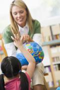 Teacher in class showing a globe with student volunteering in foreground - stock photo