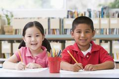 Two students in class writing - stock photo