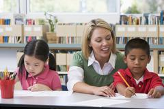 Two students in class writing with teacher helping Stock Photos