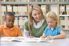 Two students in class reading with teacher Stock Photos